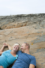 Sweden, Halland, Onsala, Couple lying on rock