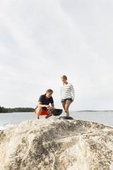 Sweden, Stockholm Archipelago, Sodermanland, Morko, Couple doing barbeque on large rock