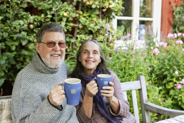 Sweden, Vastergotland, Tarby, Senior couple drinking coffee in garden