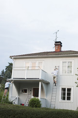 Sweden, Sodermanland, Jarna, Man and woman painting house