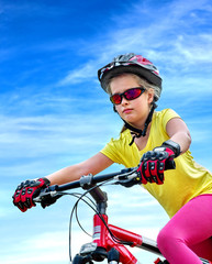 Bikes cycling child. Girl rides bicycle. Little girl in cycling. Cycling is good for child health. Cyclist look away aganist blue sky.