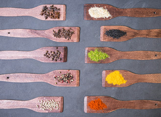 Various spices, herb,  spicy and sweet pepper, anise, sesame, coriander, wooden blades on a dark table.