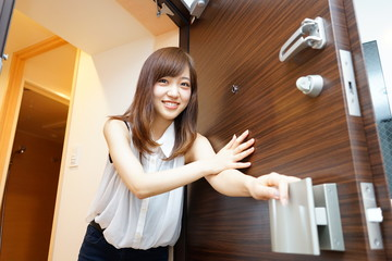 Young Japanese woman opening door for delivery service 一人暮らしの自宅玄関のドアを開ける若い女性