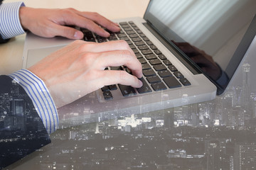 businessman typing on keyboard laptop with cityscape background