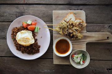 Malaysian food chicken satay with peanut sauce on wood backgroun