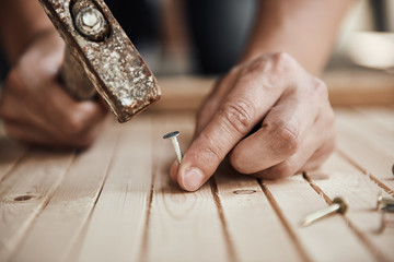 Close-up of handyman hammering a nail in wooden board. Concept of repair and renovation.