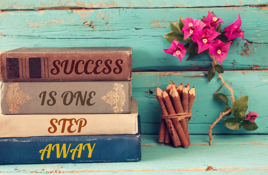 stack of books over wooden table and motivational phrase