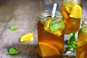Orange iced tea in a glass jar with paper straws.