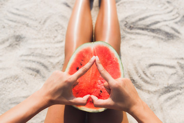 Woman with half of watermelon on beach