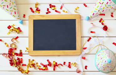 Party hat next to colorful confetti and empty blackboard