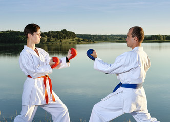 The guy and the girl in a white kimono with red and blue belts are in karate stands near the lake