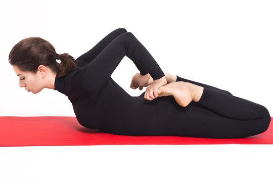 Beautiful athletic girl in black suit doing yoga. bhekasana asana - frog pose . Isolated on white background.