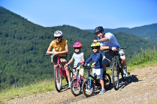 Family on a biking day, parents pointing at scenery