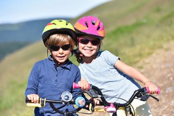 Portrait of cheerful kids riding bike