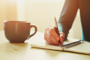 hands with pen writing on notebook with morning coffee or tea