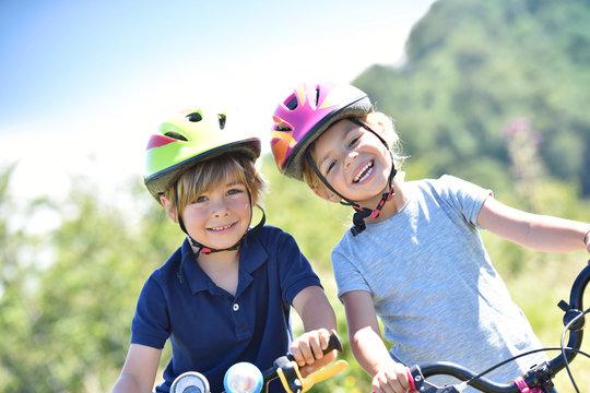 Portrait of cheerful kids riding bikes