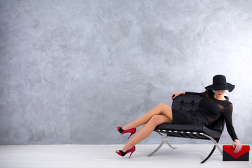Shot of a stylish woman sitting on a sofa in an empty room
