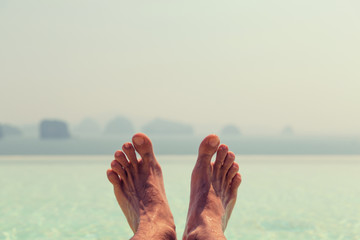 closeup of male feet over sea and sky on beach