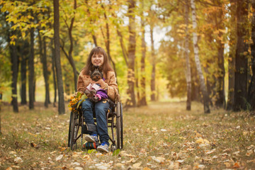 the smiling cheerful girl on a wheelchair with the dog in autumn