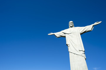 Corcovado Christ the Redeemer statue standing under bright tropical sun blue sky Rio de Janeiro Brazil