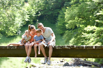 Family sitting on a bridge looking at fish in river