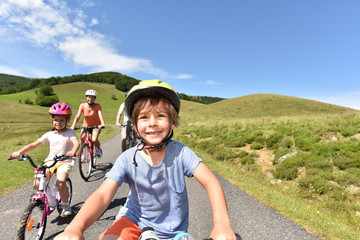 Portrait of little boy riding bike with family