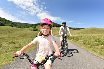 Portrait of little girl riding bike with family