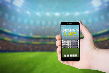 Hand hold a phone with betting online on a screen