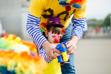 Father and little daughter in clown costume blowing bubbles outdoors at summer day