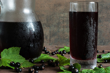 cold black currant juice in a glass and pitcher on wooden table