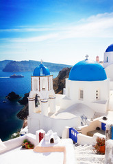 view of caldera with stairs and classical church with blue domes , Oia, Santorini, Greece , toned