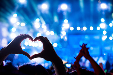 Crowd of Audience at during a concert with silhouette of a heart shaped hands shadow, light illuminated is power of music concert