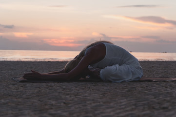 Spoed Foto op Canvas Ontspanning Young woman doing yoga at the beach at sunset.