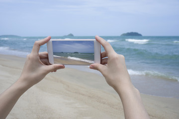 Close up of woman's hand holding smartphone, mobile, smart phone over blurred beautiful blue sea to take a photo of the sea