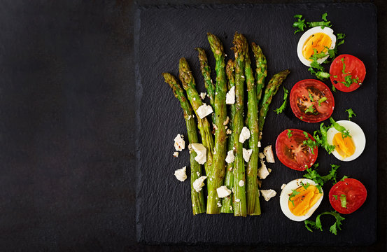 Warm salad of roasted asparagus, feta cheese, tomatoes and eggs. Top view