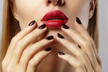 Close-up of woman's lips with fashion red make-up and manicure. Beautiful female full lips with perfect makeup. Classic visage. Part of female face. Macro shot of beautiful make up on full lips.