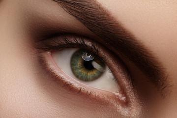 Beautiful macro shot of green female eye with natural makeup. Perfect shape of eyebrows, brown eyeshadows and long eyelashes. Cosmetics and make-up. Closeup macro shot of fashion smoky eyes visage