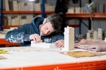 Man Sculpting Plaster Model Buildings