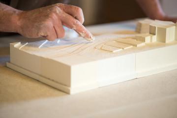 Fingers Smearing White Paint on Plaster Model
