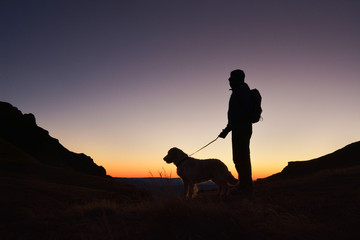 Silhouette of hiker with small backpack and his dog at sunrise