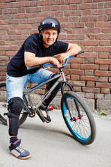 Portrait of guy in helmet on a bike sitting against the wall of red brick