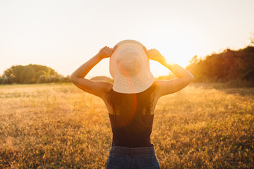 Hippie girl in nature, holding hat looking at Sun