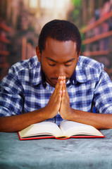 Religious man sitting while praying and reading from open book on desk in front, religion concept