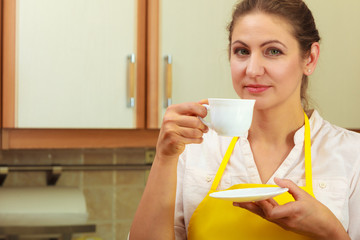 Mature woman holding cup of coffee in kitchen.