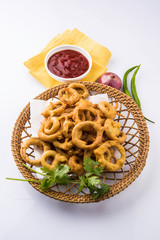 kanda bhaji in marathi or pyaj pakode in hindi or onion pakode, salty and spicy, north indian snacks,asian snacks served in terracotta bowl with tomato ketchup