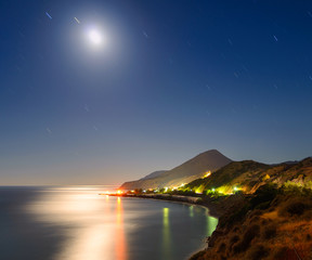 Night landscape with the moon, the sea and the stars in the sky tracks. The village of Mirtos. Crete. Greece