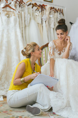 Young bride with wedding assistant making final touch on wedding dress