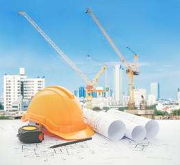 architectural blueprint with safety helmet and tools over construction site with tower crane