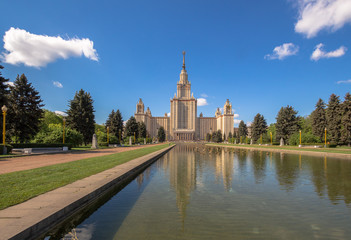 A wide angle view of water reflections of Moscow State University main building in a fountain cascade pool in a sunny summer day