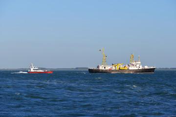 Pilot ship leading cargo ship to port